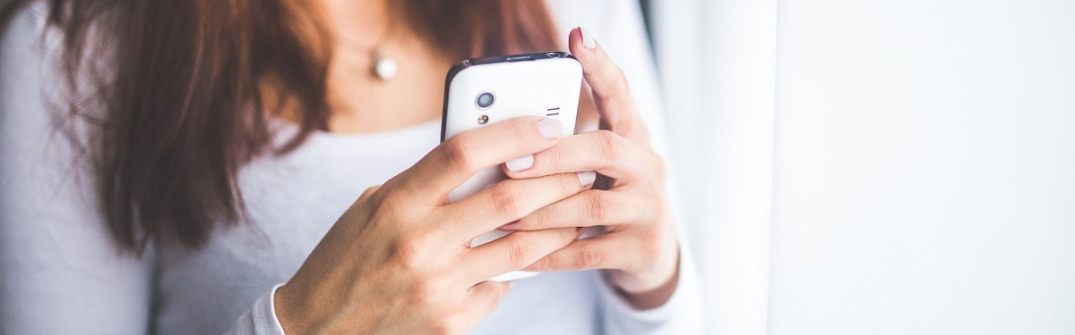 PALKO-sovellus -sivun kansikuva: Nainen pitelee käsissään valkoista älypuhelinta