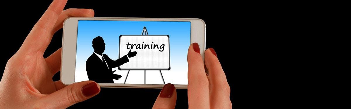 """Koulutus-sivun kansikuva: Kädet pitelevät älypuhelinta, jonka näytöllä lukee """"training"""""""